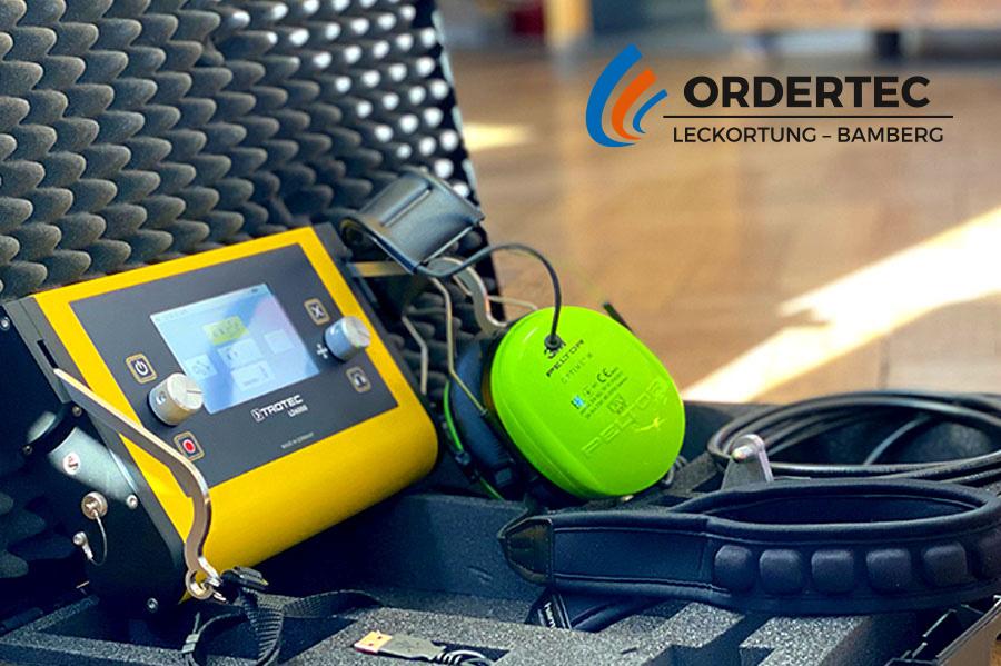 Bildausschnitt bestehend aus einem Koffer der Kopfhörer und einen rechteckigen, elektronischen Kasten beherbergt (akustisches Ortungsgerät) stehend auf einem Holzboden