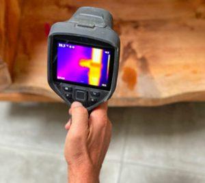 Eine Hand die eine Wärmebildkamera hält und auf einen verschwommen aufgenommen Hintergrund hält.
