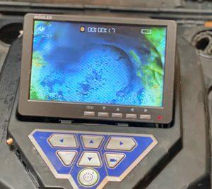 Nahaufnahme eines Bildes einer Endoskopkamera. Zu sehen sind blaue undgrüne Kraterlandschaften