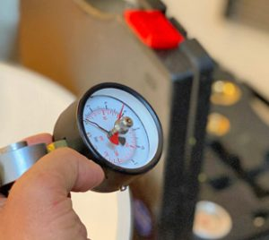 Offener Handwerkskoffer verschwommen im Hintergrund, im Vordergund ist eine Hand die eine Arg Wasseruhr bzw. Manometer hält
