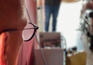 Der Blick auf einen Flur wird hier sichtbar. Links nimmt ein seitlich fotografierter Männerkopf mit Brille und sehr kurzen Haaren circa ein Drittel des Bildes ein, vor ihm sind Kartons, Handwerkerkoffer, viel Chaos und schemenhaft ein weiterer Mann sichtbar