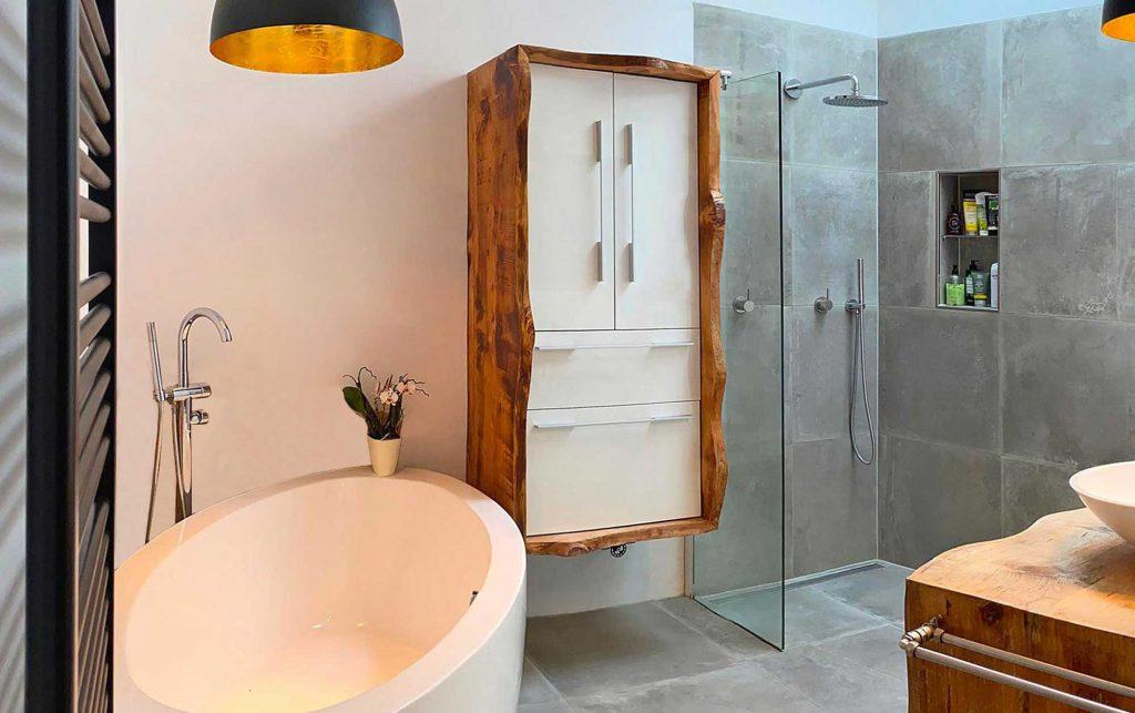 Aufnahme eines Badezimmers, Badewanne, Waschbecken und Badschrank sind weiß, der Boden hat graue Fliesen, schwarze Highlights durch zwei Lampen und eine Heizung, alles in allem wird ein Industrie-Look verkörpert