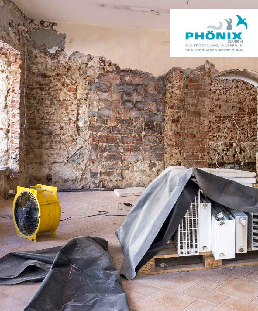 Sanierungsbedürftiges Zimmer mit abgeschlagenen Wänden; in der Mitte steht ein Lüfter und abgedeckte, demontierte Heizkörper, alles sehr in Staub gehüllt, in der rechten oberen Ecke steht das Logo Phönix Bautrocknung