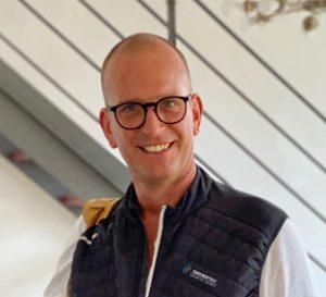Im Raum steht ein Mann mit sehr kurzen Haaren, einer Brille, freundlich lächelnd, sichtbar sind Kopf und Oberkörper. Er trägt ein weißes Shirt und eine blaue Weste mit dem Logo von Ordertec darüber.