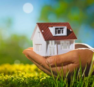Großaufnahme eines kleinen Hauses, geborgen in der Hand eines Erwachsenen. Im Hintergrund ist schemenhaft etwas Grünes und Blaues sichtbar was Wiese und Himmel andeuten sollen.