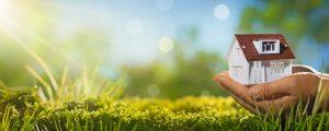 Ein kleines Haus, eingehüllt in die Hand eines Erwachsenen, Hand und somit auch Haus schweben dicht über einer strahlend grünen Wiese mit angedeuteten Sonnenstrahlen